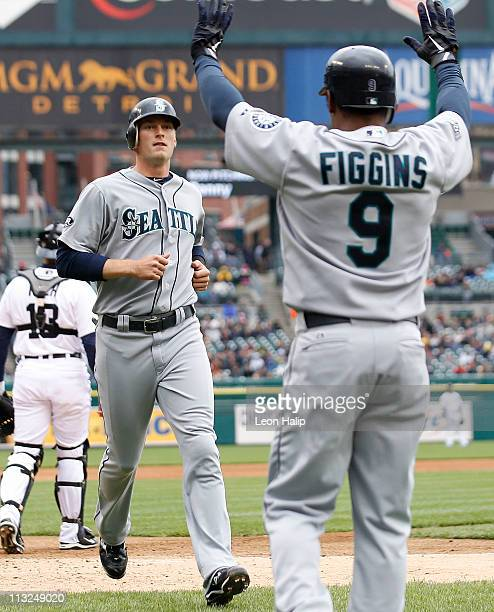 Michael Saunders of the Seattle Mariners is congratulated by teammate Chone Figgins in the fifth inning after scoring on a double off the bat of...