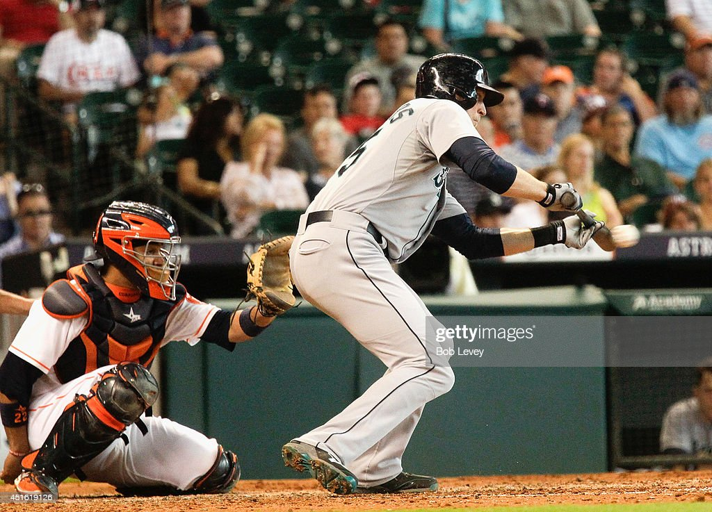 Michael Saunders #55 of the Seattle Mariners lays a bunt down in front of catcher Carlos Corporan #22 of the Houston Astros at Minute Maid Park on July 2, 2014 in Houston, Texas.