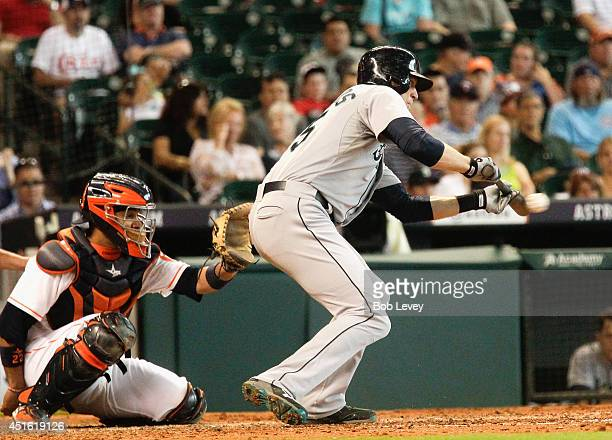 Michael Saunders of the Seattle Mariners lays a bunt down in front of catcher Carlos Corporan of the Houston Astros at Minute Maid Park on July 2...