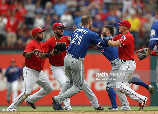 Michael Saunders of the Toronto Blue Jays and Ryan Rua of the Texas Rangers push one another after the benches cleared in the eighth inning at Globe...
