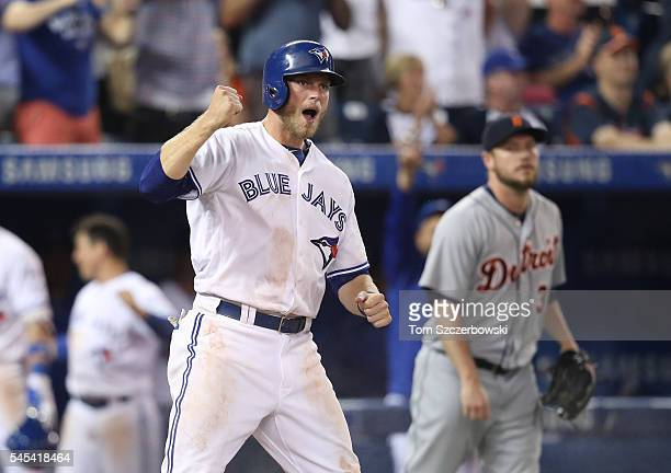 Michael Saunders of the Toronto Blue Jays celebrates as he scores the goahead run in the eighth inning during MLB game action as Alex Wilson of the...