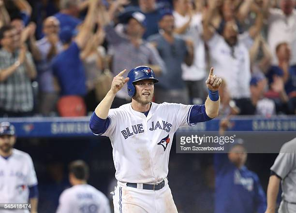 Michael Saunders of the Toronto Blue Jays celebrates as he scores the goahead run in the eighth inning during MLB game against the Detroit Tigers on...