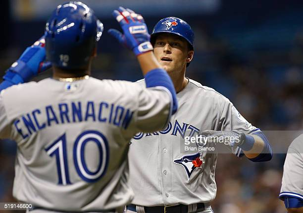Michael Saunders of the Toronto Blue Jays celebrates his tworun home run with teammate Edwin Encarnacion during the fourth inning of a game on April...
