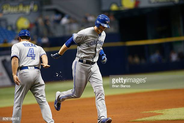 Michael Saunders of the Toronto Blue Jays celebrates with first base coach Luis Rivera as he rounds the bases after hitting a home run off of pitcher...