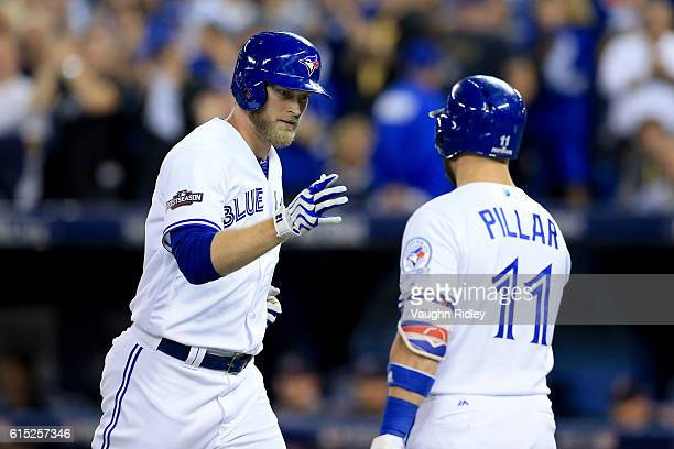 Michael Saunders of the Toronto Blue Jays celebrates with teammate Kevin Pillar after hitting a solo home run in the second inning against Dan Otero...
