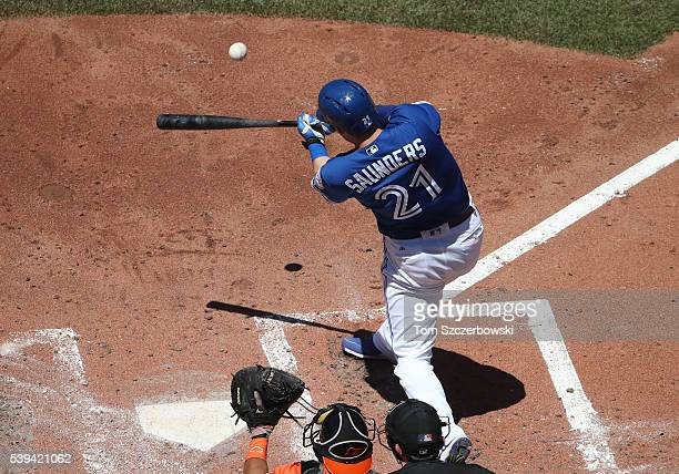 Michael Saunders of the Toronto Blue Jays hits an RBI sacrifice fly in the third inning during MLB game action against the Baltimore Orioles on June...