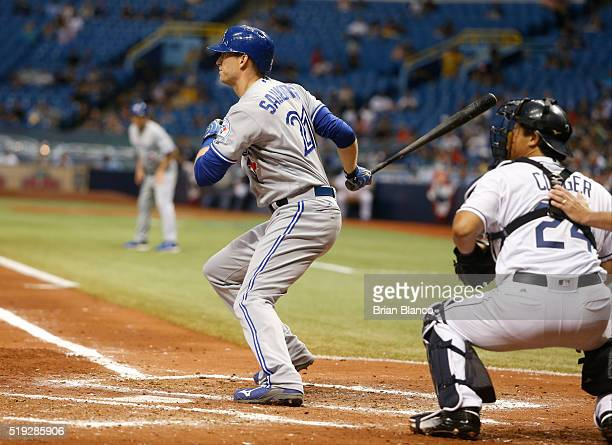 Michael Saunders of the Toronto Blue Jays hits an RBI single in front of catcher Hank Conger of the Tampa Bay Rays to score Edwin Encarnacion during...