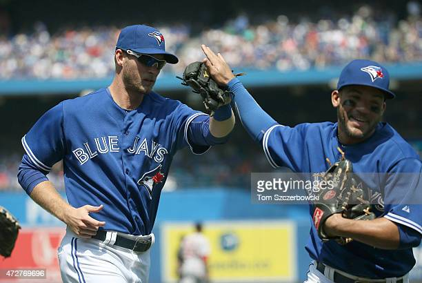 Michael Saunders of the Toronto Blue Jays is congratulated by Devon Travis after making a defensive play to end the third inning during MLB game...