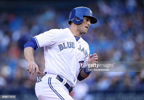 Michael Saunders of the Toronto Blue Jays scores from second base on an RBI single by Russell Martin in the first inning during MLB game action...