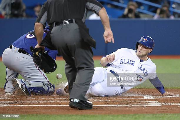 Michael Saunders of the Toronto Blue Jays slides home safely to score a run in the first inning during MLB game as Bobby Wilson of the Texas Rangers...