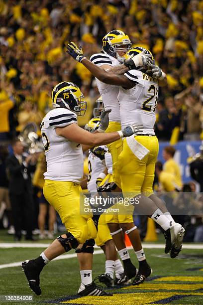 Michael Schofield Taylor Lewan and Junior Hemingway of the Michigan Wolverines celebrate after Hemingway scored a 45yard touchdown reception in the...