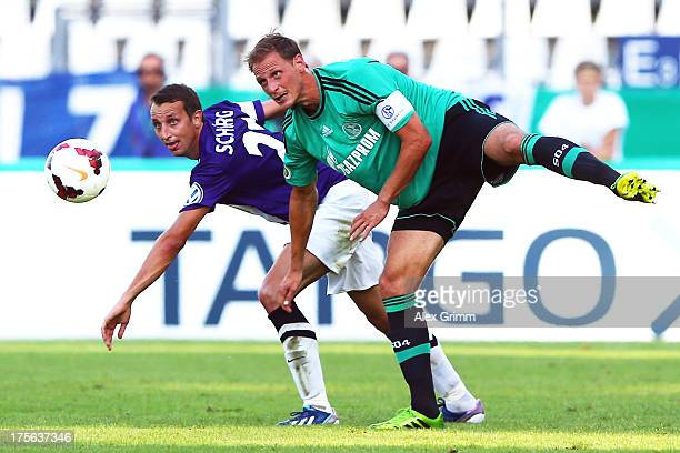 Michael Schuerg of Noettingen is challenged by Benedikt Hoewedes of Schalke during the DFB Cup first round match between FC Noettingen and Schalke 04...