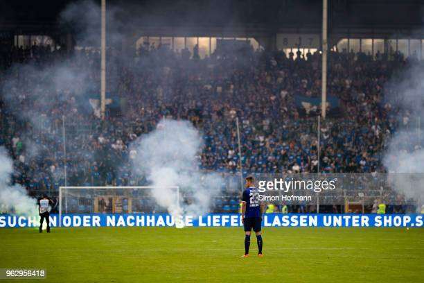Michael Schultz of Mannheimreacts as supporters of his team light fireworks during the Third League Playoff Leg 2 match between SV Waldhof Mannheim...
