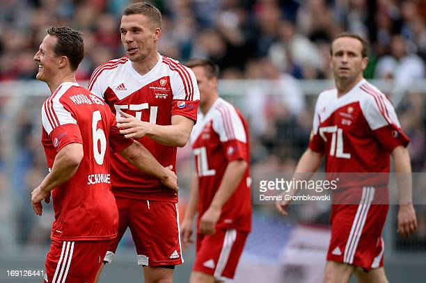 Michael Schumacher and Lukas Podolski celebrate during the 'Kicken fuer den guten Zweck' event at Sportpark Hoehenberg on May 20 2013 in Cologne...