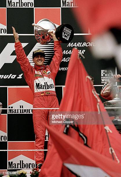 Michael Schumacher driver of the Scuderia Ferrari Marlboro Ferrari F300 raises the trophy into the air on the podium in celebration after winning the...