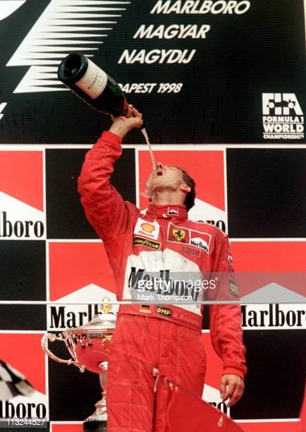 Michael Schumacher driver of the Scuderia Ferrari Marlboro Ferrari F300 pours champagne over himself in celebration after winning the Hungarian Grand...