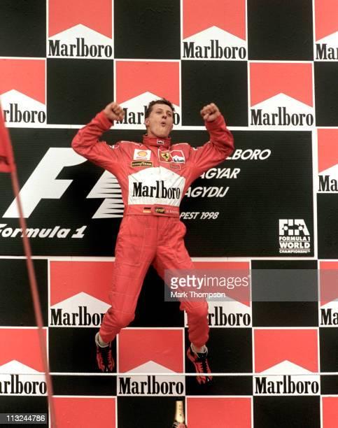Michael Schumacher driver of the Scuderia Ferrari Marlboro Ferrari F300 jumps into the air on the podium in celebration after winning the Hungarian...
