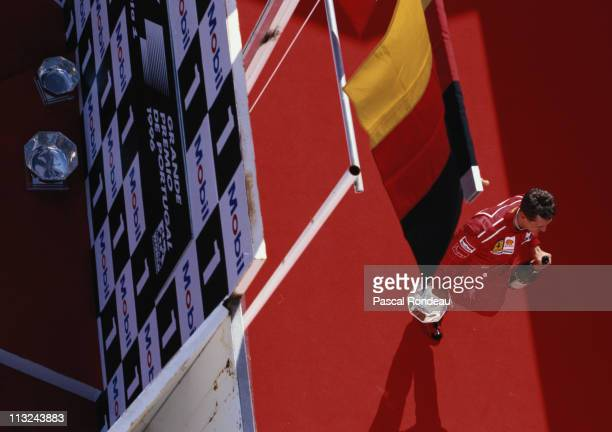 Michael Schumacher driver of the Scuderia Ferrari SpA Ferrari F310 walks away from the podium with his third place trophy and champagne after the...