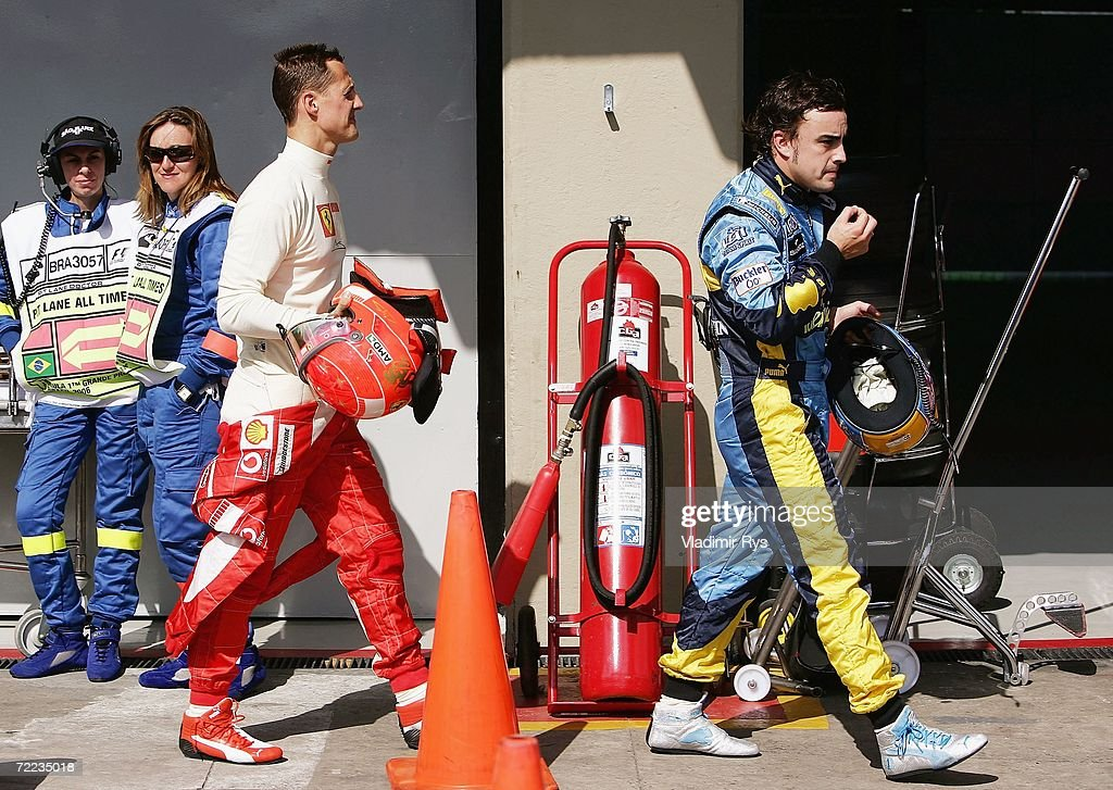 Michael Schumacher of Germany and Ferrari (L) and Fernando Alonso of Spain and Renault walk on the pit lane after the qualifying session of the Brazilian Formula One Grand Prix at the Autodromo Interlagos on October 21, 2006 in Sao Paulo, Brazil.