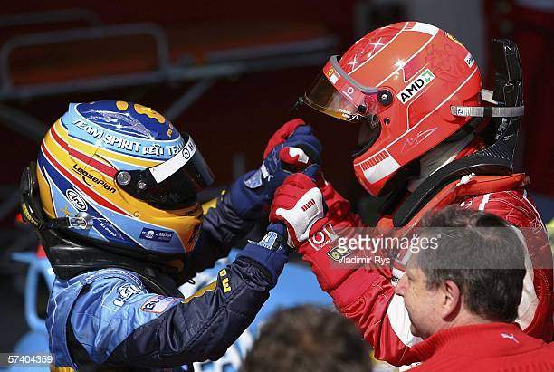 Michael Schumacher of Germany and Ferrari celebrates first place with Fernando Alonso of Spain and Renault finishing second after the San Marino...