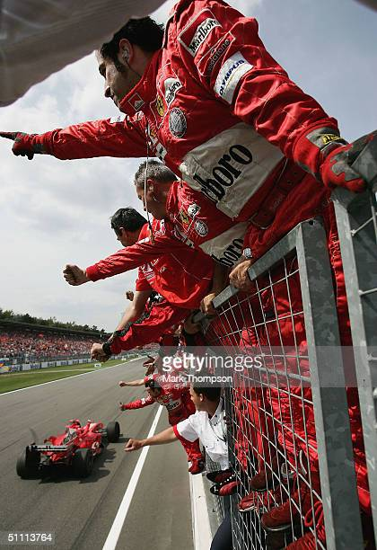 Michael Schumacher of Germany and Ferrari celebrates in front of his team-mates after winning the German F1 Grand Prix at the Hockenheim Circuit on...