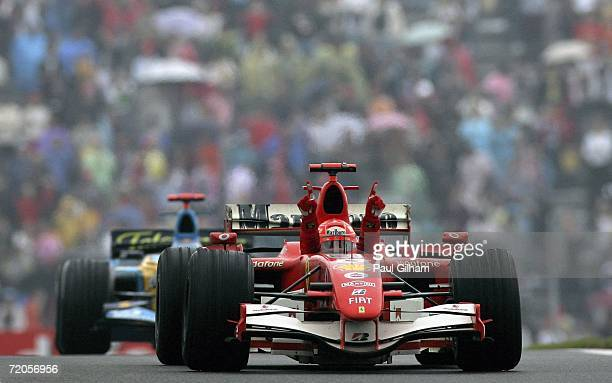 Michael Schumacher of Germany and Ferrari celebrates winning the Chinese Formula One Grand Prix as he leads Fernando Alonso of Spain and Renault into...