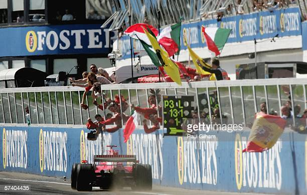 Michael Schumacher of Germany and Ferrari celebrates with his teammates as he crosses the finish line to win the San Marino Formula One Grand Prix at...