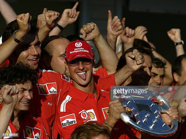 Michael Schumacher of Germany and Ferrari celebrates with his Ferrari team-mates after Ferrari won the Constructors Championship following his win in...