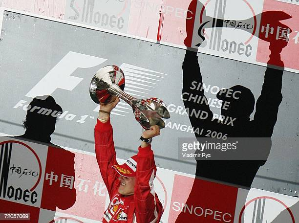 Michael Schumacher of Germany and Ferrari celebrates with the trophy as the shadow of Fernando Alonso of Spain finishing 2nd falls on the back wall...
