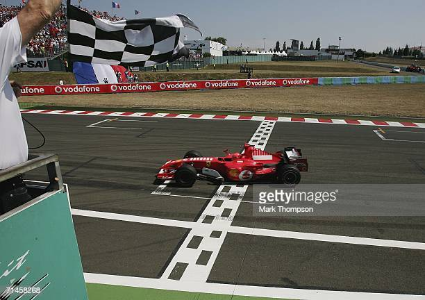 Michael Schumacher of Germany and Ferrari crosses the finish line to win the French Formula One Grand Prix at the Nevers Magny-Cours Circuit on July...