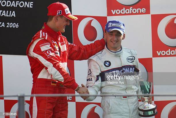 Michael Schumacher of Germany and Ferrari finishing first shakes hand with Robert Kubica of Poland and BMW Sauber finishing third during the medal...
