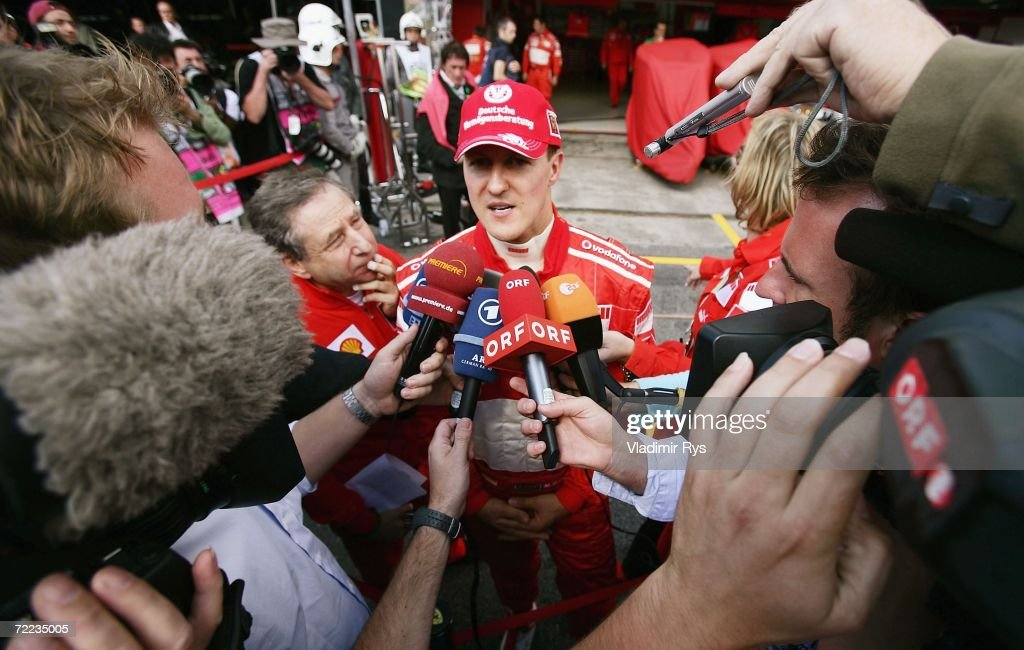 Michael Schumacher of Germany and Ferrari gives interviews as team principal Jean Todt (L) stands by after the qualifying session of the Brazilian Formula One Grand Prix at the Autodromo Interlagos on October 21, 2006 in Sao Paulo, Brazil.