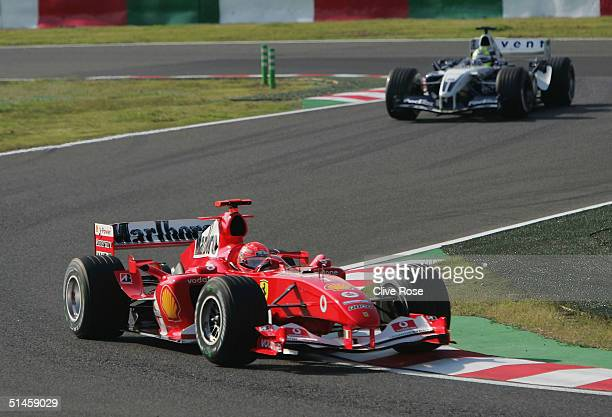 Michael Schumacher of Germany and Ferrari leads his brother Ralf Schumacher during the Japanese Grand Prix at Suzuka Circuit on October 10 2004 in...