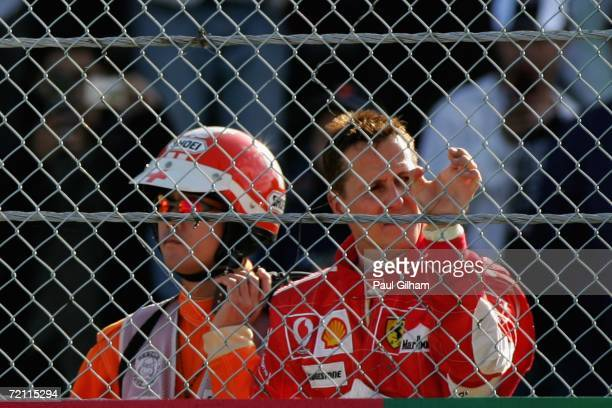 Michael Schumacher of Germany and Ferrari looks on from the side of the track after his engine failed and he retired from the race during the...