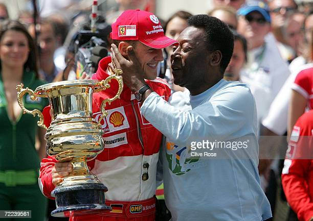 Michael Schumacher of Germany and Ferrari receives a trophy for his achievements in Formula One Grand Prix racing from Brazilian soccer legend Pele...