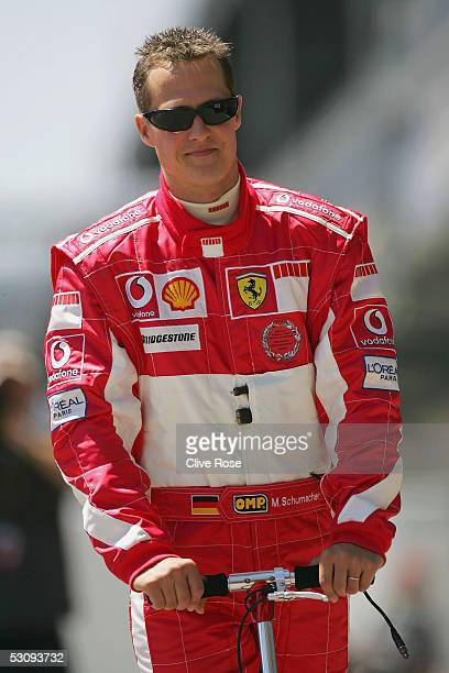 Michael Schumacher of Germany and Ferrari rides a scooter to his pit prior to the first practice session as he prepares for the United States F1...