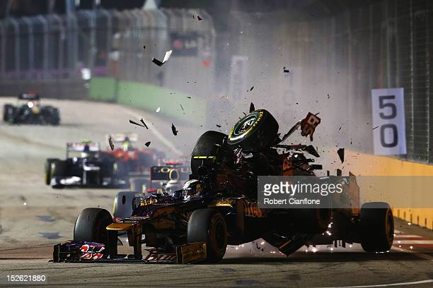 Michael Schumacher of Germany and Mercedes GP crashes into the back of JeanEric Vergne of France and Scuderia Toro Rosso during the Singapore Formula...