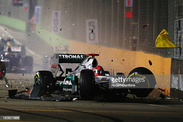 Michael Schumacher of Germany and Mercedes GP crashes into the back of Jean-Eric Vergne of France and Scuderia Toro Rosso during the Singapore...