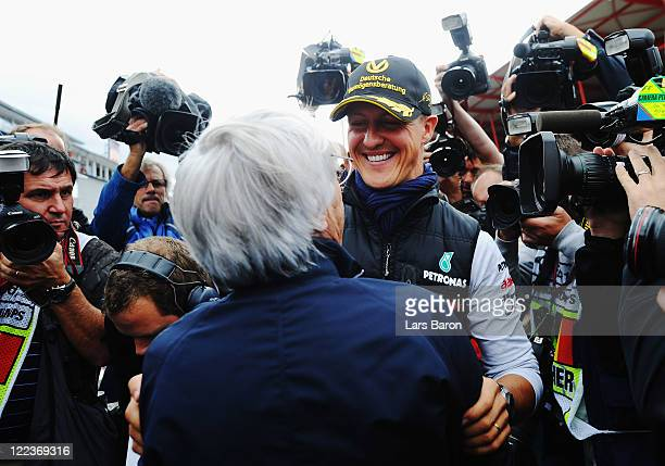 Michael Schumacher of Germany and Mercedes GP is congratulated by F1 supremo Bernie Ecclestone as he celebrates the 20th anniversary of his first...