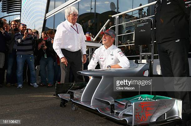 Michael Schumacher of Germany and Mercedes GP is seen with F1 supremo Bernie Ecclestone as he receives a cake and the front wing of an F1 car to...