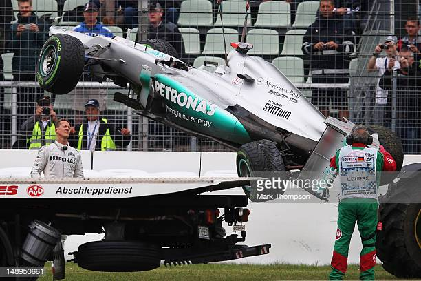 Michael Schumacher of Germany and Mercedes GP watches on as his car is removed after he span and crashed out during practice for the German Grand...