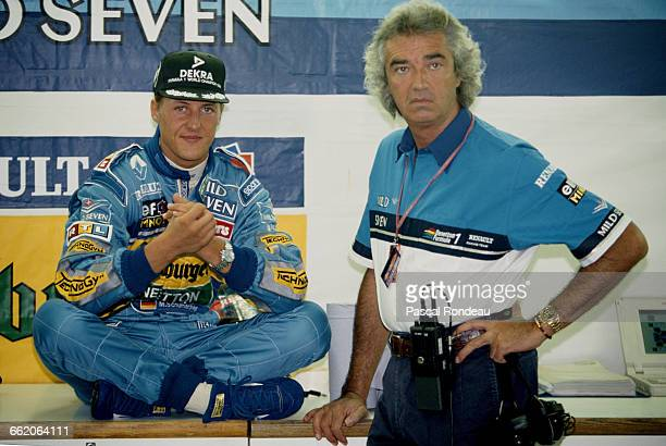 Michael Schumacher of Germany driver of the Mild Seven Benetton Ford Benetton B195 Renault V10 talking with team director Flavio Briatore during...