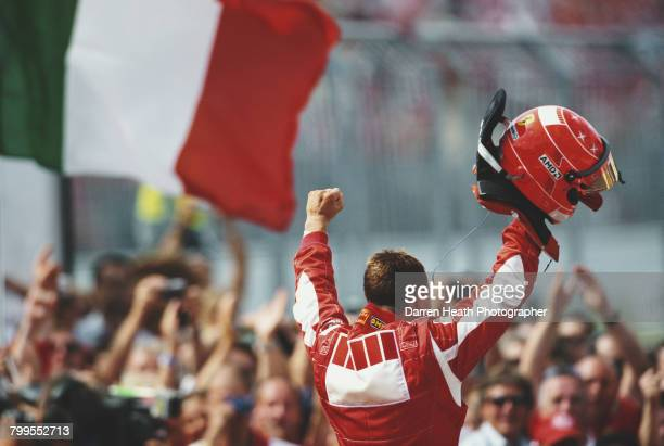 Michael Schumacher of Germany, driver the Scuderia Ferrari Marlboro Ferrari 248 F1 Ferrari V10 salutes the crowd and celebrates wiining the Formula...