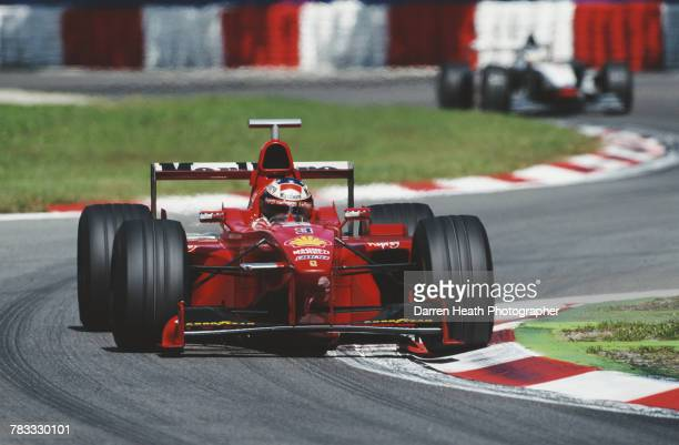 Michael Schumacher of Germany drives the Scuderia Ferrari Marlboro Ferrari F300 Ferrari V8 ahead of Mika Hakkinen during the Formula One Italian...