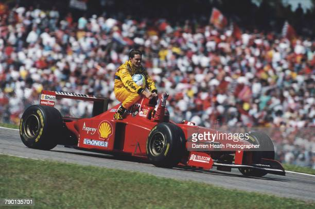 Michael Schumacher of Germany driving the Scuderia Ferrari Marlboro Ferrari F310B Ferrari V10 waves to the crowd as he gives Giancarlo Fisichella him...