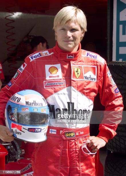Michael Schumacher substitute Finnish Ferrari driver Mika Salo poses for the photographers in the pits of the racetrack before the first free...