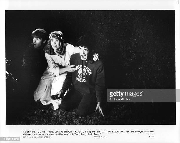 Michael Sharrett, Krysty Swanson and Matthew Laborteaux and in a row with fear on their faces in a scene from the film 'Deadly Friend', 1986.