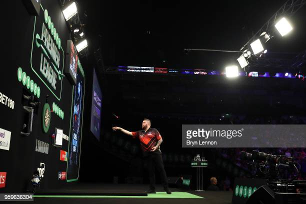 Michael Smith of Great Britain throws against Michael van Gerwen of The Netherlands during the Betway Premier League Darts PlayOffs final at The O2...