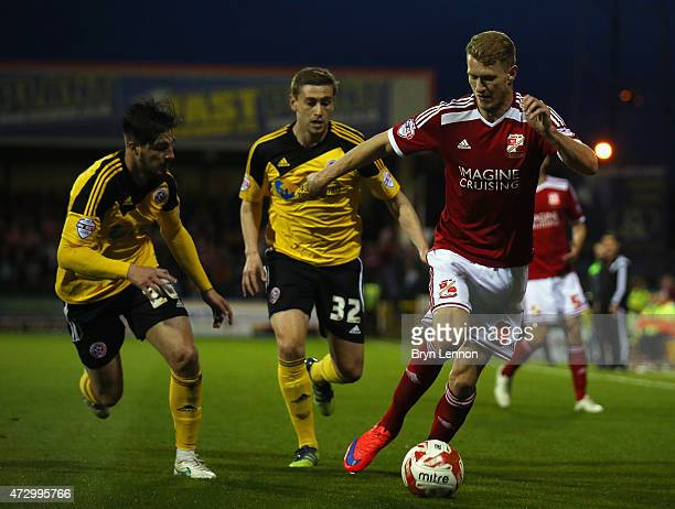 Michael Smith of Swindon Town avoids Steven Davies and Kieron Freeman of Sheffield United during the Sky Bet League 1 Playoff Semi-Final between...
