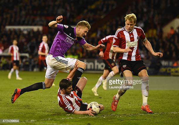 Michael Smith of Swindon Town battles with Bob Harris and Jay McEveley of Sheffield United to the ball during the Sky Bet League One playoff semi...